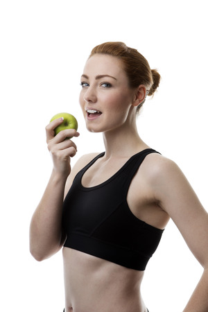 keep fit: young woman wearing keep fit clothes eating an apple