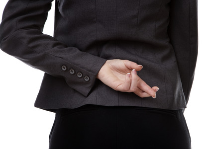 businesswoman in a suit, close up image of one hand behind her back with her fingers crossed photo