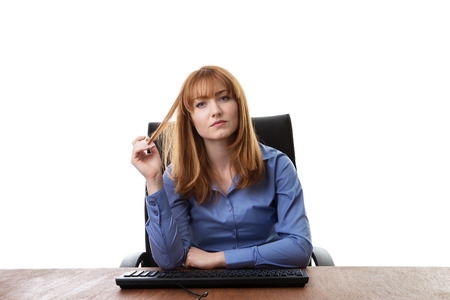 at her desk: business woman sitting at her desk not looking very happy Stock Photo