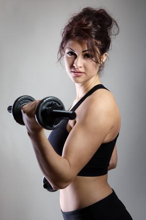strong women: Fitness model shot in the studio using dumbbells