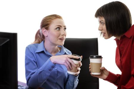 chismes: dos compa�eros de trabajo que tiene una charla y chismes en el trabajo con un caf� Foto de archivo