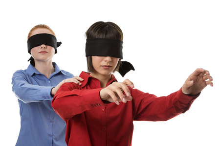 blind person: two business woman blind folded leading the other