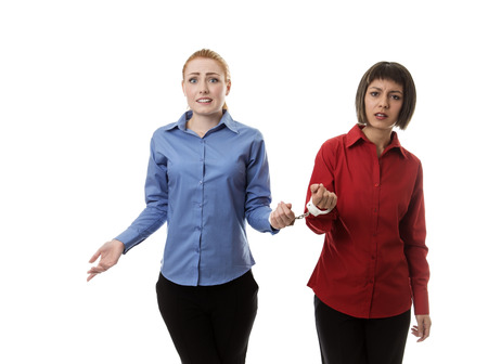handcuffed: two business woman handcuffed together Stock Photo