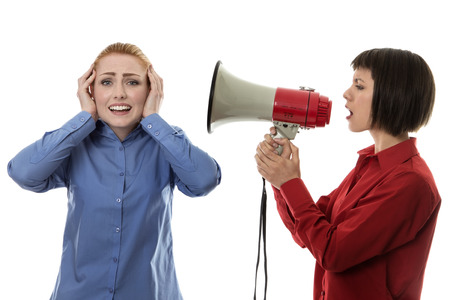 anger management: Businesswoman shouting at another woman using a bullhorn Stock Photo
