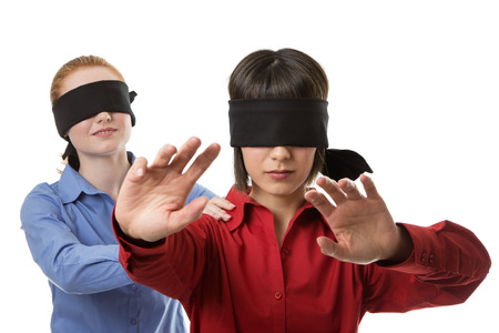 two business woman blind folded leading the other