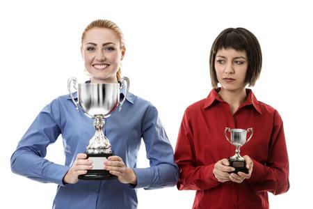 desprecio: dos mujer de negocios la celebración de un trofeo, uno es la celebración de una grande donde el otro es la celebración de una más pequeña y no parece feliz Foto de archivo
