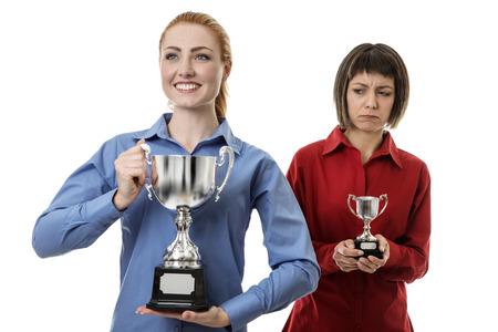 desprecio: dos mujer de negocios la celebraci�n de un trofeo, uno es la celebraci�n de una grande donde el otro es la celebraci�n de una m�s peque�a y no parece feliz Foto de archivo