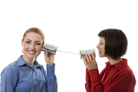 communicate: two business people using tin cans to communicate with each other