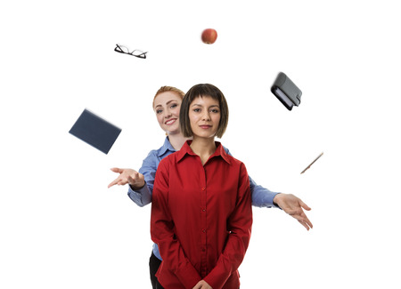 juggle: woman standing behind another woman helping her to juggle objects