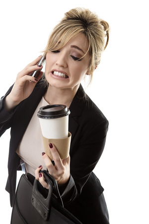 clumsy: business woman on the phone spilling her drink on her way to work