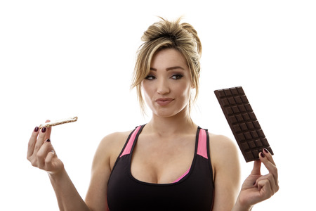 unhealthy thoughts: fitness woman holding a chocolate bar and a healthy crispbread snack not sure what to eat
