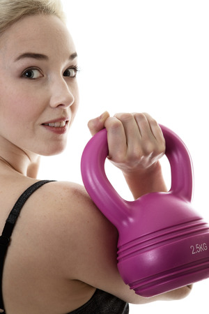 single woman: single woman using a kettlebell weight to keep fit