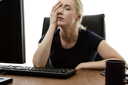 woman sitting at her desk with her head in her hands stressed out Stock Photo