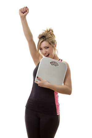 woman on scale: happy fitness woman holding scales Stock Photo