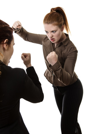 violence in the workplace: two business woman fighting each other at work Stock Photo
