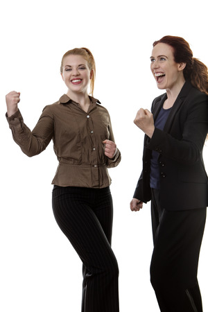 celebrate: two happy and successful business woman with there arms up in the air