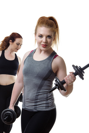 keeping fit: two woman working out and keeping fit lifting weights Stock Photo