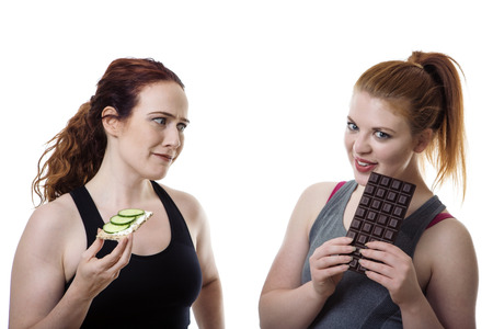 healthy choices: two fitness woman one eating healthy and the other is eating chocolate Stock Photo