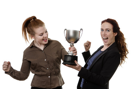 hold up: two business woman hold up a large trophy looking happy