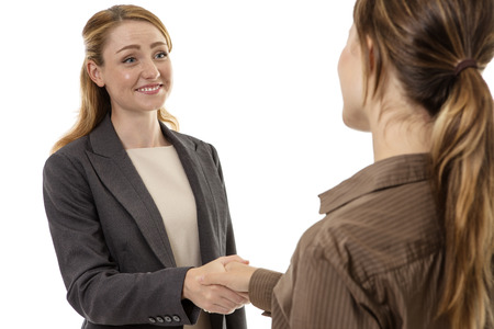 welcome people: Two business woman shaking hands together