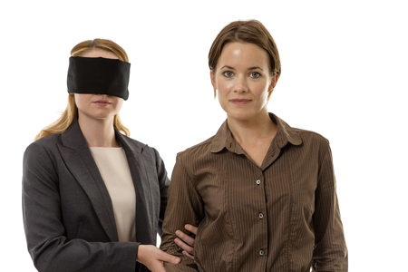 blindfolded: two business woman one blindfolded and the other helping Stock Photo