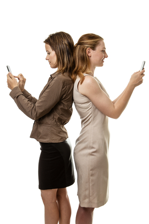 woman standing back: two business woman standing back to back texting each other