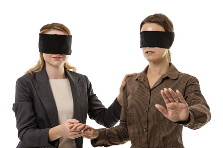two business woman one blindfolded and the other helping Stock Photo