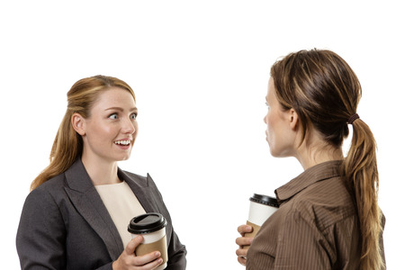 Two business woman chatting and enjoying a gossip over a coffee together Stock Photo