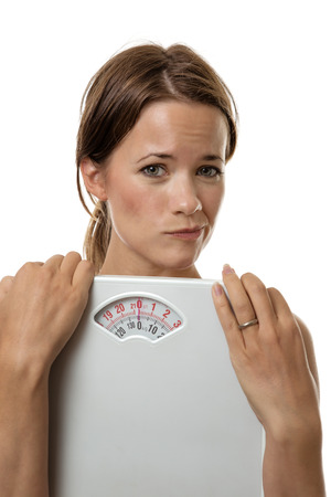 unsure: fitness woman holding scale unsure and afraid to weight herself Stock Photo
