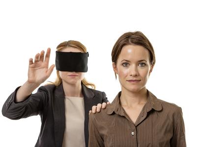 ojos vendados: dos mujeres de negocios de una con los ojos vendados y la otra ayuda