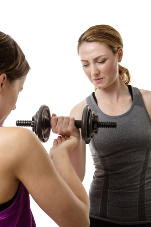 encouraging: two fitness woman one helping and encouraging the other to lift weights doing a workout Stock Photo