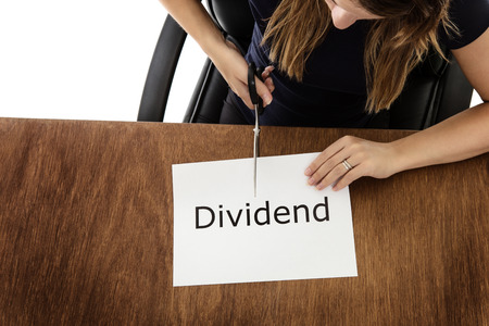 dividend: woman shot from above cutting paper in half with the word dividend written on