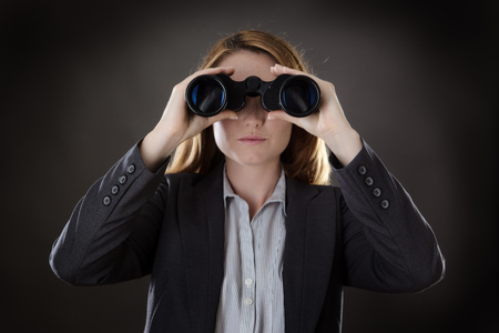executive search: business woman looking through binoculars shot in the studio on gray background Stock Photo