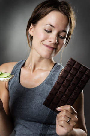 temptation: woman holding a crispbread in one hand and a large chocolate bar in the other will she give into temptation