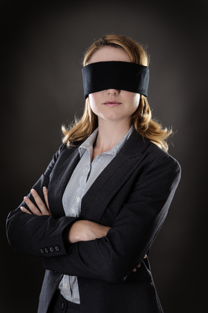 portrait of a business woman blind folded shot in the studio on gray background