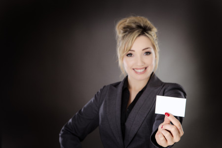 businesscard: business woman holding up a businesscard shot in the studio on a gray background.
