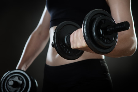 midriff: close up shot of a woman midriff working out using dumbbells shot in the studio on a gray background