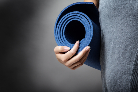 close up shot of woman holding a yoga mat up to her midmidriff