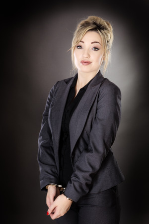 business woman,  handcuffed shot in the studio on a gray background