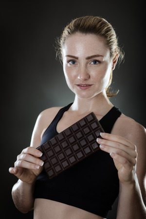 cravings: fitness woman holding a large bar of chocolate