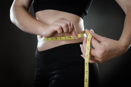 cintura: dispararon cerca de la mujer que sostiene cintura una cinta métrica alrededor de su cintura disparo en el estudio sobre un fondo gris