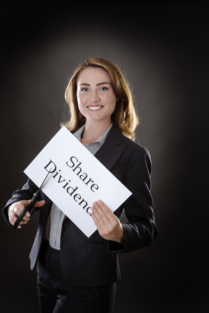 dividend: business woman cutting paper in half with the word Share Dividend written on it, concept idea shot in the studio on gray background
