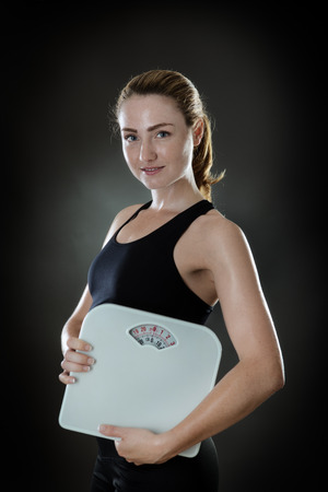 scales thin: woman holding scale shot in the studio on gray background