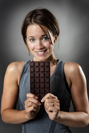 temptation: fitness woman holding a large bar of chocolate will she give into temptation