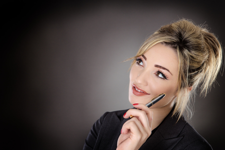 bussines people: thinking business woman holding a pen shot in the studio on a grey background