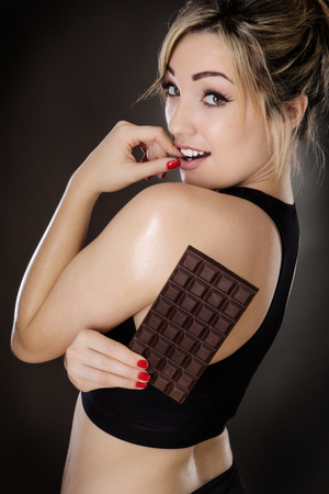 tempted: fitness woman being tempted by chocolate shot in the studio on a grey background