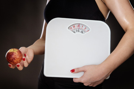 midriff: close up shot of woman midriff holding scale and a apple