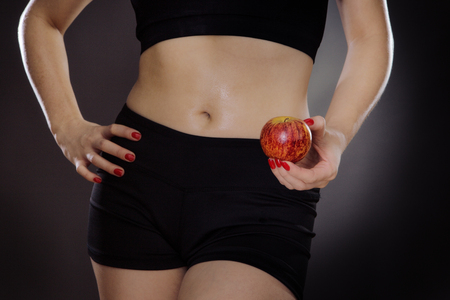 midriff: close up shot of womans midriff holding a apple shot in the studio on a gray background