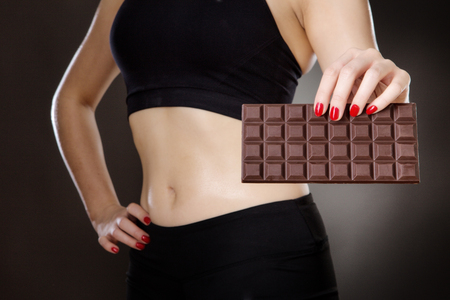 midriff: close up shot of womans midriff holding a chocolate bar studio on a gray background