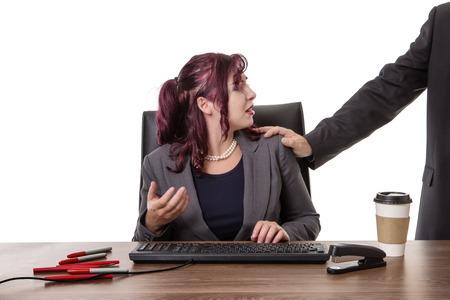 secretaresse zit aan bureau met een mans hand op haar schouder voelde ongemakkelijk Stockfoto